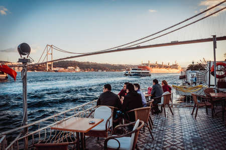 istanbul beach: ISTANBUL, TURKEY -  october 23, 2014: people are drinking tea in a cafe with Bosphorus bridge view  in Istanbul, Turkey. Editorial