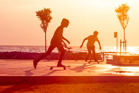 Young skaters training in the park near the sea in sunset. Toned picture Stockfoto