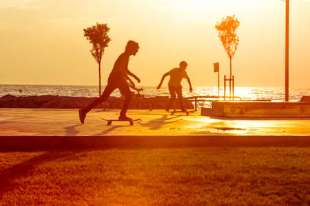 skaters: Young skaters training in the park near the sea in sunset. Toned picture Stock Photo
