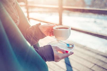 sunny day: Taza de caf� caliente o t� en las manos en invierno fr�o d�a soleado. Foto virada