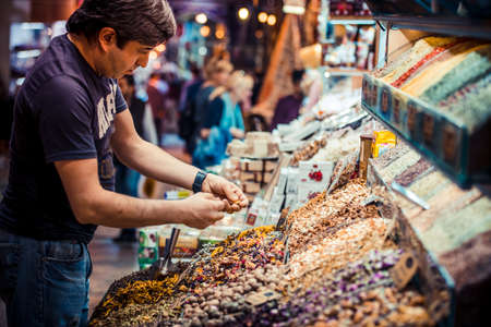 spice market: ISTANBUL, TURKEY -  october 26, 2014: Vendor is selling spices and tea at Spice market in Istanbul, Turkey.