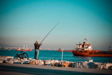 ISTANBUL, TURKEY, October, 26, 2014: Man is fishing on Marmara sea quay in Bakirkoy in Istanbul, Turkey.