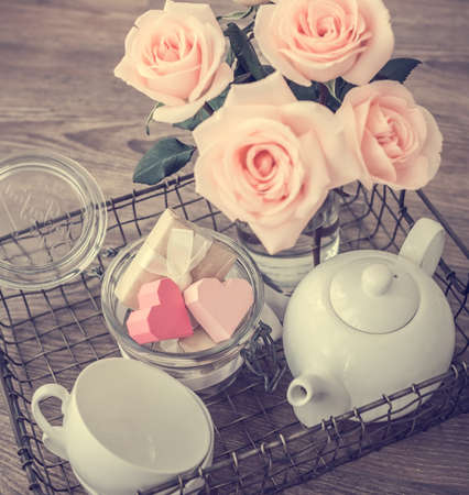 rose coloured: Tray with roses, white teapot, cups and valentines paper hearts in retro jar. Toned picture