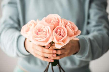 美しいピンクのバラの花束を持って手。トーンの画像