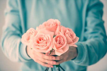 dar un regalo: Manos que sostienen el ramo de rosas rosadas hermosas. Foto virada