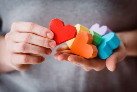 lgbt: Hands holding  rainbow paper hearts, LGBT symbol. Toned picture