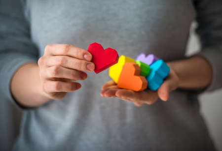 Hands holding  rainbow paper hearts, LGBT symbol.