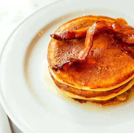 bacon and eggs: American pancakes with syrup and crispy bacon Stock Photo