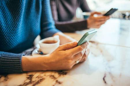 people: Dos personas que utilizan tel�fonos inteligentes en el caf� Foto de archivo