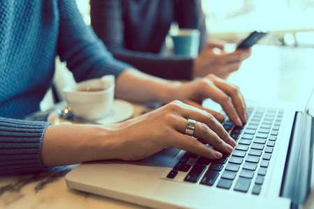 Manos femeninas que pulsan en el teclado de la computadora portátil en café. Foto virada Foto de archivo