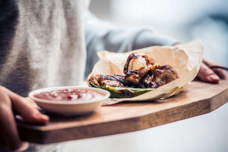 bbq chicken: Fried buffalo chicken wings on wooden board. Toned image