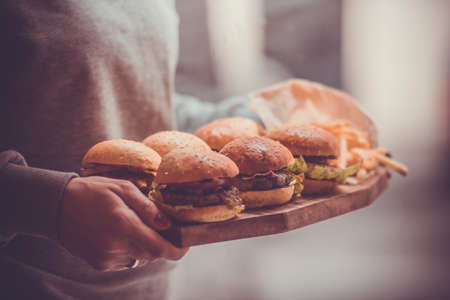 classic burger: Party set of different burgers on wooden board. Toned image Stock Photo