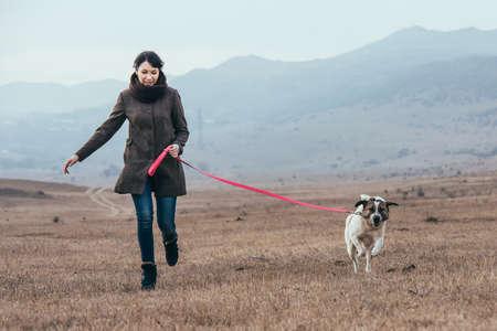 perro corriendo: La muchacha bonita wailking con su perro