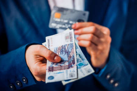 roubles: Business person holds russian roubles and plastic credit card