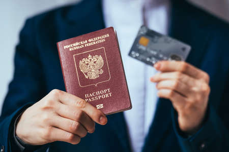 Business person holds russian passport and plastic credit card