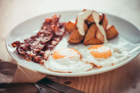 bacon and eggs: Fried eggs, backon and potato with sauce for breakfastToned image