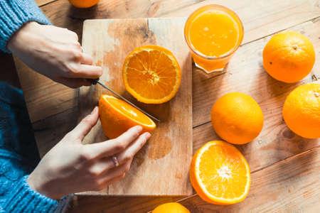 naranjo: Persona de corte para hacer jugo de naranjas frescas en la mesa de madera