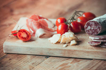 Appetizers - tomato, meat and cheese - on wooden board. Toned image Фото со стока - 37897781