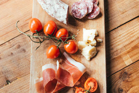 Appetizers - tomato, meat and cheese - on wooden board Фото со стока