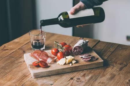 jamon y queso: Aperitivos - tomate, carne y queso - en tabla de madera con una botella de vino y vidrio. Imagen entonada Foto de archivo