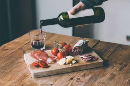 wine country: Appetizers - tomato, meat and cheese - on wooden board with bottle of wine and glass. Toned image