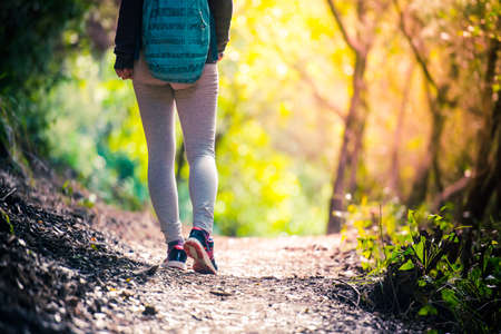 Walking or running legs on trail, adventure and exercising in forest at sunset photo