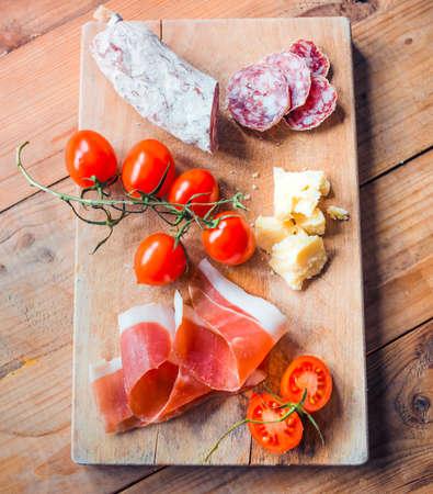 jamon y queso: Aperitivos - tomate, carne y queso - en tabla de madera