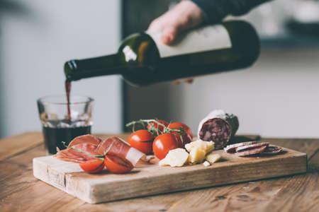 tapas españolas: Aperitivos - tomate, carne y queso - en tabla de madera con una botella de vino y vidrio. Imagen entonada Foto de archivo