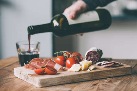 tomate: Entr�es - tomate, viande et fromage - sur planche de bois avec bouteille de vin et le verre. Image teint�e Banque d'images