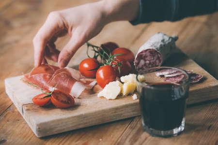 alcool: Apéritifs - tomate, viande et fromage - à bord en bois avec verre de vin. Image teintée Banque d'images