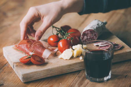 restaurant food: Appetizers - tomato, meat and cheese - on wooden board with  glass of wine. Toned image Stock Photo