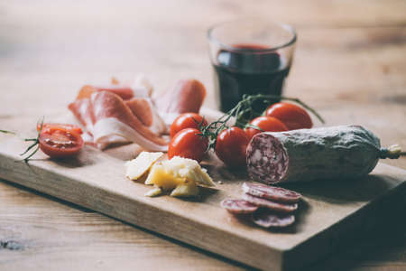 Appetizers - tomato, meat and cheese - on wooden board with  glass of wine. Toned image Imagens