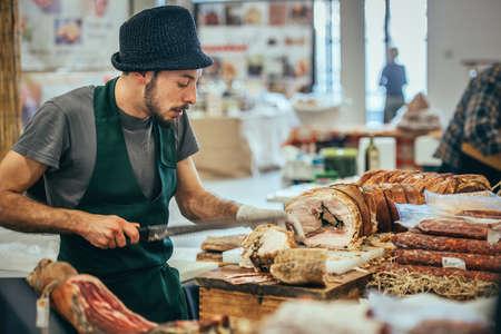 GENOA, ITALY - FEBRUARY 15, 2015: Unidentified butcher slicing italian pork roast porchetta at food market in Genoa, Italy Editöryel