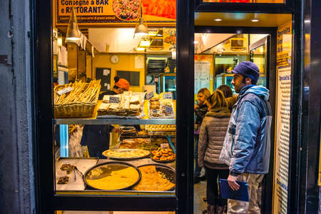 ovenbaked: GENOA, ITALY - FEBRUARY 23, 2015: People buy fresh baked rustic bread focaccia at the rural bakery. Genoa is famous for its traditional focaccia alla genovese
