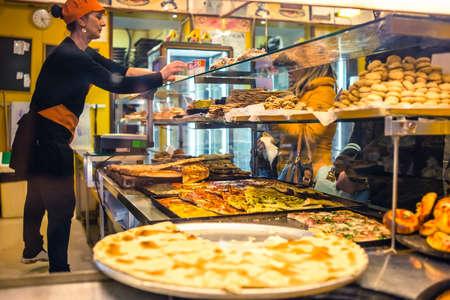 Genua, Italië - 23 februari 2015: De niet geïdentificeerde vrouw verkoopt vers gebakken boerenbrood focaccia op de landelijke bakkerij. Genua is beroemd om zijn traditionele focaccia alla Genovese