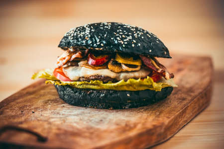 Modern black burger on wooden board. Toned picture