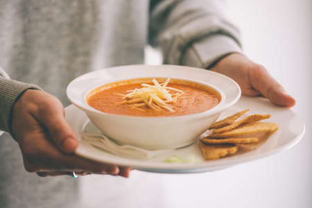 cold soup: Plate of tomato soup served with cheese and toasts in hands. Toned picture