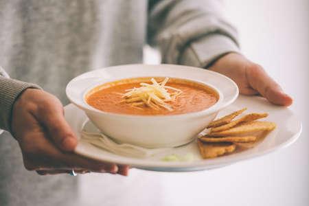 Plato de sopa de tomate servido con queso y tostadas en las manos. Foto virada Foto de archivo - 39078186