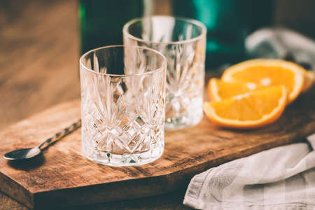 whisky glass: Two empty cocktail glasses and orange slices. Toned image Stock Photo