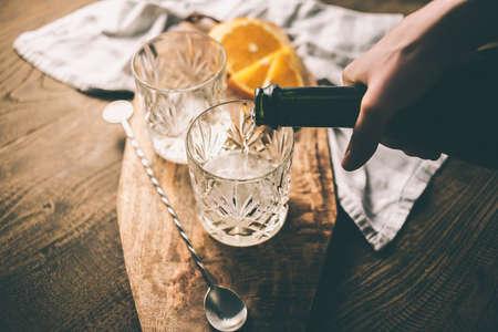 Gießen Champagner oder Wein in ein Glas für die Herstellung einer Cocktail. Getönt