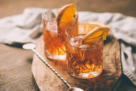 cocteles: Dos vasos de cóctel con una rodaja de naranja. Imagen entonada Foto de archivo