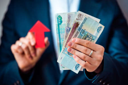 roubles: Business person holds roubles and red arrow