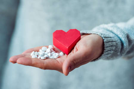 birth control pill: White pills and paper heart in hands. Medicine and health care concept Stock Photo