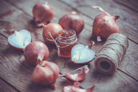 marmalade: Red onion marmalade in a small glass jar on wooden table. Toned image Stock Photo