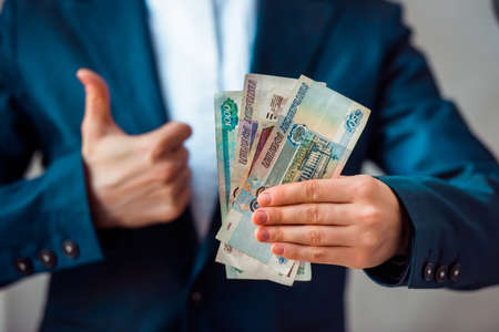 roubles: Business person holds roubles and shows thumb up Stock Photo