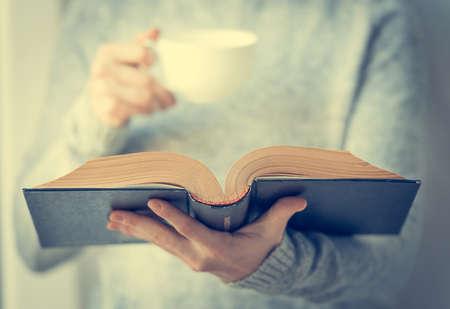Jeune femme lisant un livre et tenant une tasse de thé ou de café. Image tonifiée Banque d'images - 39078907