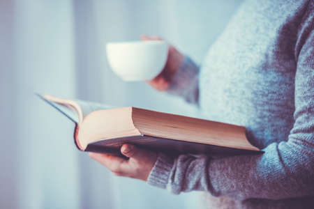 reading: Young woman reading a book and holding cup of tea or coffee. Toned image Stock Photo