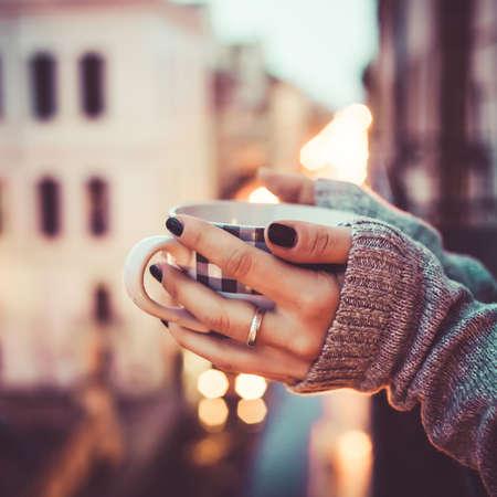 Kopje thee of koffie in handen op wazige romantische achtergrond. Gestemd beeld