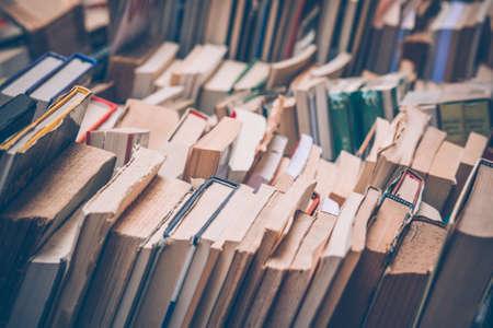 Muchos libros antiguos en una librería o biblioteca. Imagen entonada Foto de archivo