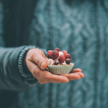 small cake: Small cake with strawberry in hand. Toned image Stock Photo